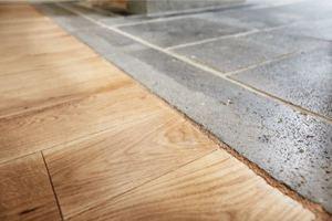 Detail: Auf dem Fußboden treffen Basaltsteinplatten von Spritzkork getrennt auf Eichendielen