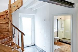Links: Die alte Holztreppe wurde vom Schreiner aufgearbeitet und wieder eingebaut. Auf dem Fußboden treffen  Basaltsteinplatten von Spritzkork getrennt auf Eichendielen