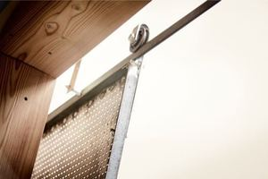 Detial: Die Verschattung erfolgt über Lochblechtafeln, die verschiebbar an Scheunentorrollen am Dach hängen