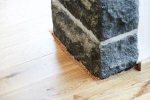Detail: Trennung des Fußbodenbelags aus Eichen-Dielen mit Spriztkork von den aufgehenden Wänden