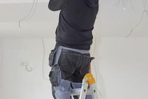 """Rechts: Jürgen Koch bei der Montage des Deckenprofils für das Ganzglastrennwandsystem """"quint-it"""""""