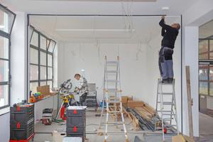 """Jürgen Koch montiert gemeinsam mit Michael Kummer das Ganzglastrennwandsystem """"quint-it""""<span class=""""bildnachweis"""">Fotos: Robert Mehl</span>"""
