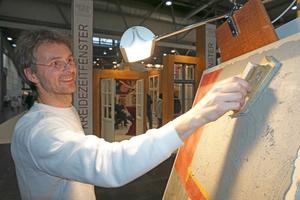 Ulrich Bettentrup zeigt auf dem Stand der Firma Kreidezeit den Putzauftrag für die Herstellung von Stuccolustro