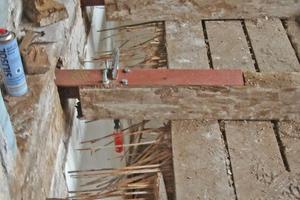 Der Zimmermann hat die Deckenbalken von oben geschlitzt und kraftschlüssig über Stahlprofile mit dem Mauerwerk verbunden
