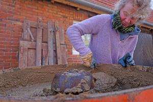 Zimmerin Gaby Lipka mischt den Lehmputz in einem alten Tellermischer der Marke Atika an