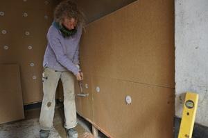 Rechts: Zimmerin Gaby Lipka schlägt Nägel in die Dämmstoffdübel