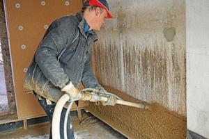Lehmbauer Andreas Beermann zieht den frischen Lehmputz mit einer Kartätsche ab