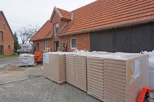 Rechts: Vor dem ehemaligen Stall stehen Holzfaserdämmplatten und Säcke mit Lehmputz bereit