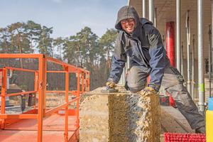 Simon Pock von Erden Lehmbau raut ein bereits gesetztes Stampflehmelement auf und bereitet es dadurch für das Auftragen des Lehmmörtels vor