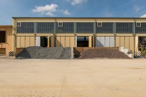 In der ehemaligen Fahrzeughalle werden die Stampflehmwände hergestellt. Vor der Halle sind Schaumglasschotter (links) und Lava-Schotter (rechts) aufgehäuft<br />