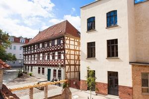 Links im Bild das zum Hotel umgebaute 430 Jahre alte Fachwerkhaus, rechts das Fabrikgebäude der ehemaligen Möller'schen Handschuhfabrik in Arnstadt
