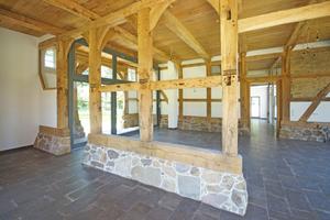"""Blick ins Erdgeschoss mit offener Fachwerkwand auf einem der Deelendurchfahrt im Gebäude folgenden Natursteinsockel<span class=""""bildnachweis"""">Fotos: Spooren Architekten</span>"""