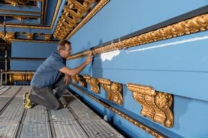 Diplom-Restaurator Piotr Slupczynski nimmt die prachtvollen Wandverzierungen im Blauen Saal genauer unter die Lupe