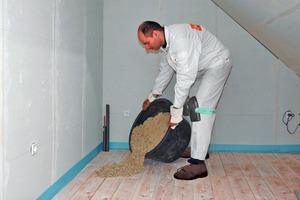 Die im Eimer mit Wasser angemischte gebundene Schüttung wird auf den Rohboden gekippt und damit der erste der beiden Dämme ausgebildet