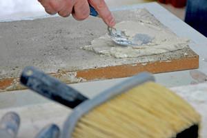 Rechts: Die Feinputzschicht aus Kalk, Sand und Wasser wird aufgezogen