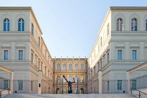 """Die beiden Seitenflügel auf der Rückseite bilden zusammen mit dem Hauptgebäude einen Innenhof, in dem die Skulptur """"Jahrhundertschritt"""" des Künstlers Wolfgang Mattheuer ihren Platz fand"""
