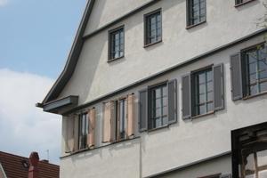 Die Fassade erhielt neue Fenster mit Öffnungsflügeln. Im komplett neuen Treppenhaus aus Beton (links) sind Festverglasungen und stilisierte Klappläden