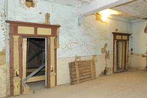 Raum mit verputzter Fachwerkinnenwand vor Beginn der Sanierungsarbeiten