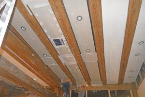 """Im großen Ratssaal wurden zwischen den repräsentativen Balkenlagen Deckenfelder aus einer Lage """"Rigips Bauplatten RB"""" erstellt und in den Lüftungsbereichen mit umlaufenden Schattenfugen versehen"""