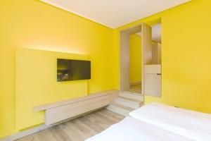 Gelb gestrichenes Hotelzimmer