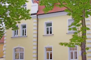 """Mitte: Die Fassadenprofile von NMC geben diesem Gebäude seine ursprüngliche Anmutung wieder. Die Fenster wurden mit Rahmenprofilen und Schlusssteinen sowie Fensterbankprofilen gestaltet. An den Hausecken sind zusätzlich, entsprechend der """"alten"""" Skizze, Bossensteine montiert worden"""