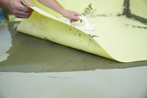 Im Bodenbereich: Einlage der zugeschnittenen Bahnen aus weber.tec 825 nach gleichem Prinzip wie im Wandbereich