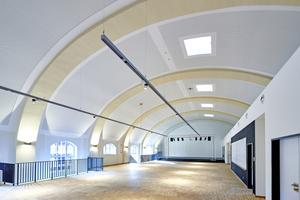 Die Tonnendecke der Mehrzweckhalle einer Hamburger Berufsschule sorgt dank des Akustikdeckensystem Knauf Cleaneo Akustik linear für gute Akustik und Raumlufthygiene