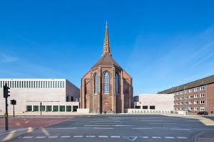 """Die neuen Baukörper, die das Langhaus der Kirche gerade so flankieren, dass nur noch der schmale Chor aus dem Ensemble heraustritt, werden durch eine helle Ziegelsteinfassade bestimmt<span class=""""bildnachweis"""">Foto: Matthias Jäger</span>"""