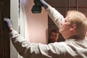 Mitarbeiter der Werkstätten Dickerhoff GmbH bei der Montage einer Tür von Schörghuber