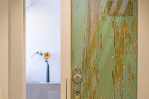 Perfekt in das Blatt einer Schiebetür hinter Glas eingebaute alte Kabinentür