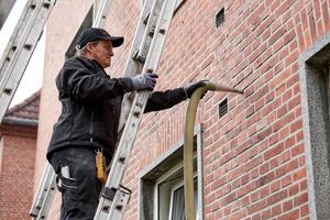 """Mit Druckluft wird das flexible """"Fillrock KD"""" Dämmgranulat in den Hohlraum zwischen Außenwand und Vormauerwerk geblasen"""