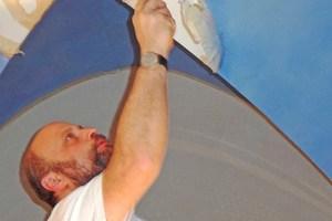 Links: Künstler Tobias Kammerer konzentriert bei der Arbeit in der Kirche St. Dionysius