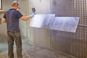 """Links: Guido Grundhoff grundiert die Treppenwangen mit """"Remmers PUR CL-240/30 in RAL 7016"""" mit Metalliceffekt"""