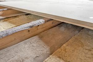Auf den Auflagedämmstreifen der seitlich angeschraubten Holzbohlen verlegten die Handwerker schwimmend die Bodenelemente