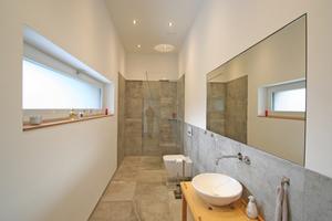 Kein Gestückel: Wandverlauf und Armaturen des Gäste-Badezimmers orientieren sich am Fliesenmaß