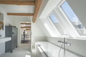 Im Bad befindet sich die Badewanne direkt unter zwei großen Dachfenstern