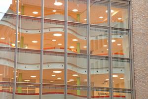 Blick vom Innenhof durch die Glasfassade in die offene Galerie des Gesundheitszentrums