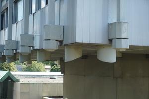 Unteres Ende der Stahltbetonzüge vor der Fassade, unter dem Gebäude das Ende der Stahlzüge im Gebäude