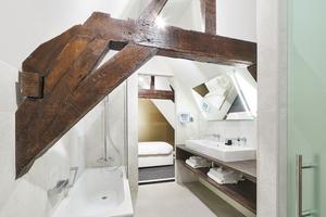 Selbst im Bad der Junior-Suite sind Teile des Dachtragwerks sichtbar erhalten geblieben<br />