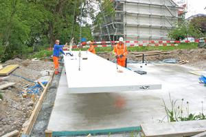 Die fünf Betonbodenelemente werden per Kran verlegt