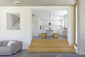 Zum neuen Wohn-/Esszimmer im ebenerdigen Anbau führt eine flache Sitztreppe von der alten Küche hinunter