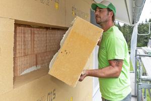 Stuckateur Christian Dressel zeigt, wie es geht. Hier setzt er gerade die mit Klebemörtel versehene Holzweichfaserdämmplatte an