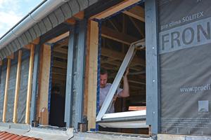 Das vorbereitete Fenster wird in den Baukörper eingesetzt. Im Holzbau ist dann die Fensterbefestigung auf einfache Weise mit direkter Verschraubung möglich. Die Klebebänder verbinden die Dichtebenen sicher miteinander