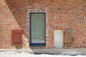 Neu ins Mauerwerk geschnittene Fensteröffnung. Links und rechts davon alte Öffnungen, die zugemauert wurden – mit den originalen Stalltüren davor