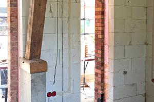 Links: Innenschale aus Porenbetonsteinen. Der neue Sichtbetonsockel, auf dem der Fuß der Strebe sitzt, wurde auf Perimetersteinen gegossen