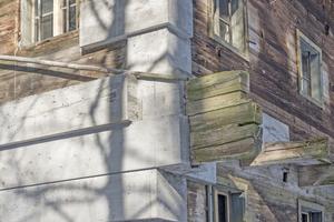 Rechts: Die eingefügten Betonbarren vertragen sich mit dem Holz der alten Fassade, weil Dämmbeton und Holz sehr ähnliche bauphysikalische Eigenschaften hat, was den Wärmedurchgangskoeffizienten und Elastizitätsmodul anbelangt