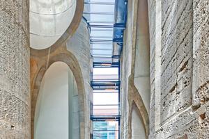 Durch die Glaskuben auf den <br />aufgeschnittenen Röhren und durch verglaste Fugen zwischen den Gebäudeteilen gelangt reichlich Tageslicht ins Atrium