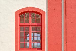 """Dunkelrote Anstriche an Eckquadern, Fenster- und Türgewänden gliedern die Architektur. Für diesen Anstrich eignete sich besonders eine wasserabweisende, dabei gleichermaßen dampfdiffusionsoffene Fassaden-Emulsionsfarbe<span class=""""bildnachweis"""">Fotos: Andreas Braun / Caparol</span>"""