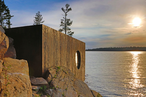 Von außen ist der Baukörper der Sauna gradlinig mit verkohlten Zedernholzbrettern beplankt