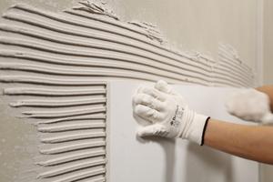 Die KlimAir Panels 1866 rückseitig mit dem Klebespachtel dünnschichtig abziehen. Optional kann je nach Untergrundrauigkeit der Klebespachtel auf der Plattenrückseite auch mit der Zahnkelle 8 x 8 x 8 vorgelegt werden. Die KlimAir Panels 1866 in das Kleberbett einsetzen. Die Panels müssen vollständig mit Kleber benetzt sein. Hohlstellen sind durch festes Andrücken bzw. Festklopfen (z.B. mit Reibebrett) zu vermeiden